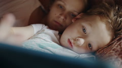 Mother and son with pad before bedtime Stock Footage