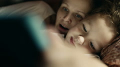 Mother and son playing on tablet PC before bed Stock Footage