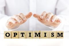 man shielding the word optimism with his hands - stock photo