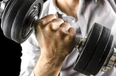 Closeup of businessman lifting weights. over black background. Stock Photos