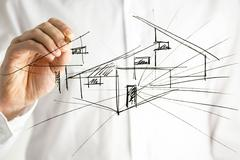 Man drawing house plan on virtual screen. Stock Photos