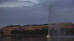Alster Lake Artezian well fountain twilight nightfall cityscape Hamburg skyline Stock Footage