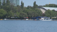 Blue water in park lake, ferry boat sitting anchored near dock, glass building - stock footage