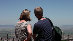 Tourists admire panorama above the town, mature couple, vacation, landscape - stock footage