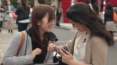 Tokyo women using mobile device on shopping street - stock footage