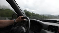 Man driving on a fenced motorway on a rainy day Stock Footage