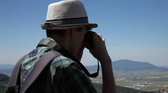 Young man looking into binoculars, admiring nature, tourist, panorama view Arkistovideo