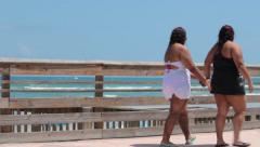 Overweight Women in Bathing Suits on the Beach Boardwalk Stock Footage