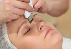 Woman under procedure of ultrasonic facial cleaning Stock Photos