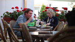 Hungry young couple eating pizza, drinking beer, restaurant, outdoors Stock Footage