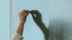 Teacher writes with chalk on a blackboard - stock footage