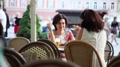 Best friends, two women smoking and drinking beer, restaurant, outdoors Stock Footage