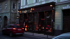 Chick cafe in old European town, exterior, old fashion pub, club, evening traffi Stock Footage