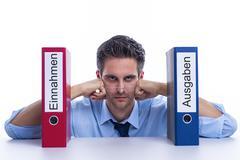 Pensive businessman with folder In German Language revenue - stock photo