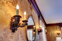 wall with antique candelabrums and mirror - stock photo