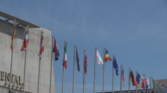Wind blowing hoisted flags, landmark building view, high importance conference Stock Footage
