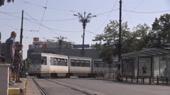 Old tram reaching station, people on pedestrians refuge streetcar taking a curve Stock Footage
