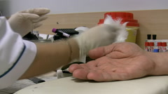 Nurse collecting blood sample from fingerprick Stock Footage
