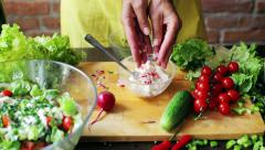 Woman adding radish and chives to the cheese and mixing it, closeup Stock Footage