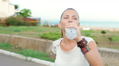 Attractive athletic girl sitting on a bike drinking water from a bottle Stock Footage
