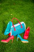 Two pairs of green and red shoes and bag lay on the grass Stock Photos