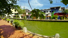 MELAKA - JUNE 2014: River and colorful buildings with tourist boat passing by. Stock Footage