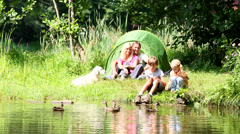 Family of four standing by the lakeside, feeding ducks Stock Footage