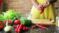 Woman cutting cherry tomatoes on the chopping board, closeup Stock Footage
