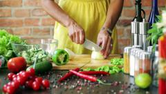 Woman cutting onion in the kitchen, closeup Stock Footage