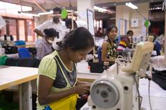 local women working on sewing machine in apparel industry - stock photo