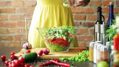 Woman adding cucumber to the salad, closeup Stock Footage