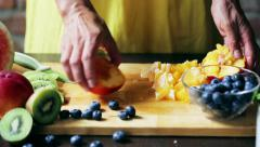 Woman cutting peach on the chopping board, closeup Stock Footage