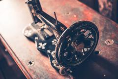 Vintage iron made sewing machine on aged wooden desk.vintage technology Stock Photos