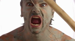 Primitive bow, primitive man doing fierce facial expressions and grimaces Stock Footage