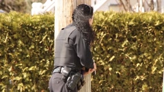 Female police officer with gun hiding behind wooden pole Stock Footage