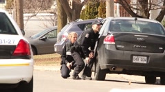 Blond officer with gun drawn peaking at camera Stock Footage