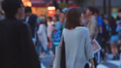 Japanese people crossing the street outside the fam Stock Footage