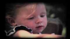 Young girl playing with cards in garden at table, vintage 8mm film Stock Footage