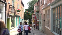Tilt and zoom up to shop sign as pedestrians walk along steep hill, lincoln, Stock Footage