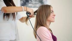 Hairdresser using straightener on beautiful woman hair in hair salon HD - stock footage