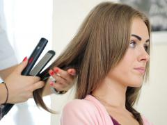 Hairdresser using straightener on beautiful woman hair in hair salon NTSC - stock footage