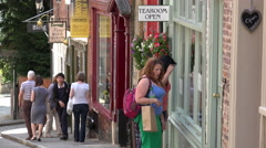 Tilt and zoom up to shop signs as pedestrians walk along steep hill, lincoln, Stock Footage