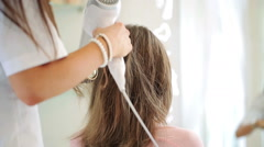 Hairdresser drying client hair with blow-dryer in hair salon HD Stock Footage