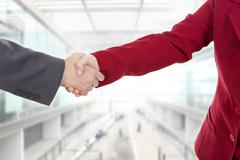 Business couple shaking hands at the office Kuvituskuvat