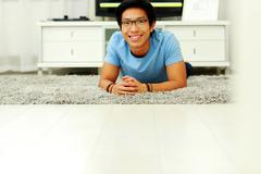 Happy asian man lying on the floor at home Stock Photos