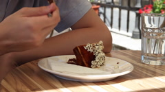 Young man eating a chocolate cake, delicious dessert, cafe terrace, summer day Stock Footage