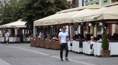 Sidewalk cafe, street restaurants , eating out, people smoking, European town Stock Footage
