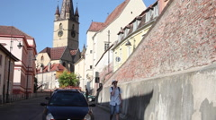 Young man talking on phone, tourist, street, clock chutch tower, medieval town Stock Footage