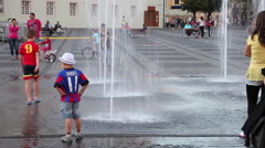 Hot summer day, children playing, water, fountain splashing, heatwave - stock footage