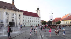 People in central square, happy kids playing, fountain, medieval town, Europe Stock Footage